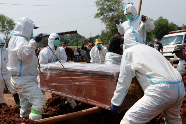 Gravediggers bury a coffin at a Muslim burial area provided by the government for COVID-19 victims in Bekasi, on the outskirts of Jakarta, on Wednesday. © Reuters